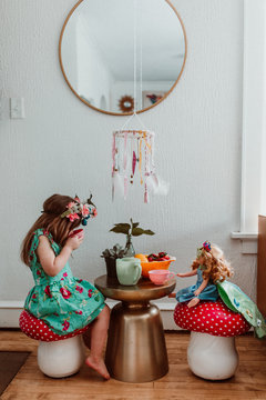 Little girl and doll having a tea party at home with flowers