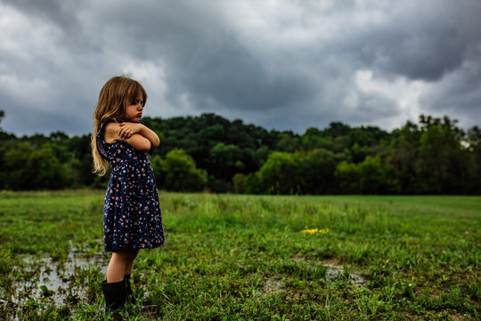 Side view of girl standing in wet field