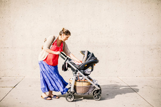 Side view of mom who stop in street to take care of baby in stroller