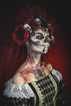 Santa Muerte Young Girl with Artistic Halloween Makeup and with Sculls