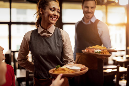 Happy waiters serving food to their guests in a restaurant.