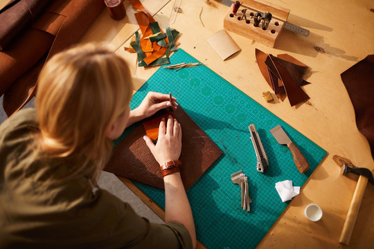 Above view portrait of female artisan making leather bag in leatherworking atelier lit by sunlight, copy space