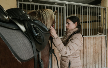 Side view of young woman in jacket putting saddle on horse