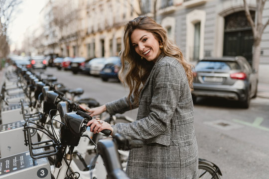Side view of attractive female in stylish coat cheerfully smiling and looking at camera while choosing rental bicycle on parking lot on city street