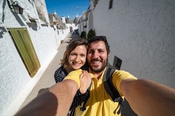Happy tourist couple walking narrow streets of Apulia region and making selfie in south of Italy