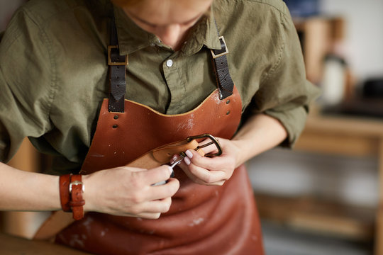 Mid section portrait of woman artisan making leather belt in leatherworking shop , copy space