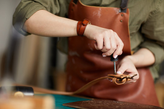 Mid section portrait of female artisan making leather belt in leatherworking shop , copy space