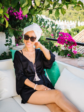 Chinese young rich woman in black satin dressing gown and towel in head resting in a balcony enjoying beautiful views on a sunny bright morning