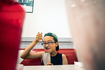 A young boy eating a milkshake for desert inside a restaurant.