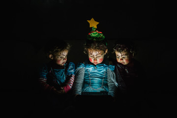 three cute little girls with princess costumes looking at a computer display against a black background