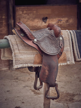 Retro leather saddle and soft pads hanging on beam near stable on ranch