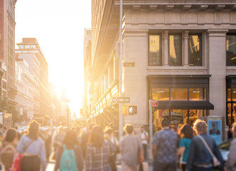 Fotomurales - Crowd of anonymous people walking down the busy sidewalk on 23rd Street in Manhattan, New York City with bright light of sunset