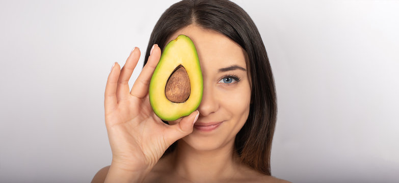 beautiful brunette girl, blue eyes, in hand avocado, white background