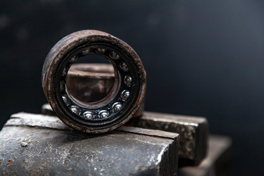 A close-up of a metal car spare part bearing from a supported car on a metal table in a car repair shop