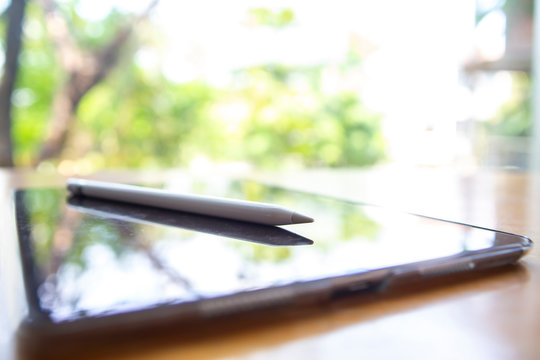 Apple pencil  with Reflecting Black tablet iPad Pro 10.5 inch on wood table, Bokeh green garden background, Perspective view, Close up shot, Selective focus, Technology, Business concept