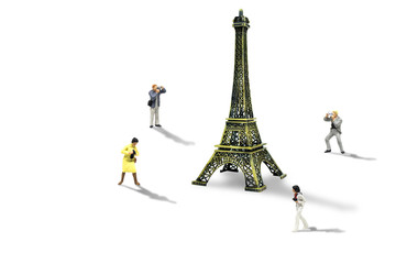 Vacation and Holiday Trip Concept : Miniature figurine character as travelers taking photograph Eiffel Tower model isolated on white background.