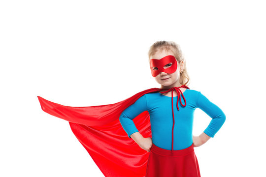 Girl child plays in a superhero red cloak in the wind.