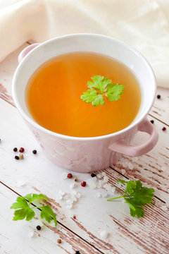 Cooked hot bone broth with spices and fresh herbs. Medical dietary broth and superfood. For ketogenic diet and paleo diet. Serve on an individual plate on a wooden background and with a white napkin.