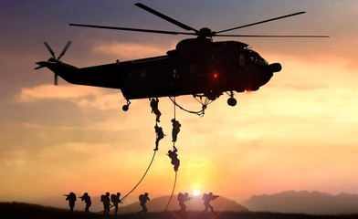Stores photo Hélicoptère Military commando helicopter drops in silhouette during sunset