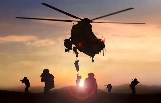 Special force assault team helicopter drops during sunset