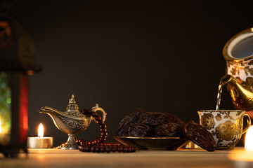 Ramadan food and drinks concept. Ramadan Lantern with arabian lamp, wood rosary, tea, dates fruit and lighting on a wooden table on dark background.