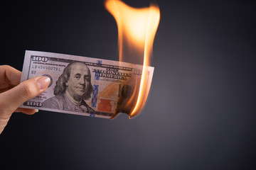 Woman hand holding burning burning dollar cash money over black background - business finances, savings and bankruptcy concept.