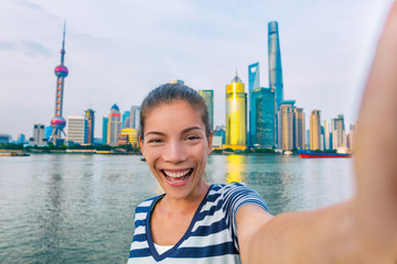 Wall Mural - Selfie Asian tourist chinese woman China travel. Smiling young girl excited holding smartphone camera to take a picture with phone of herself in front of Shanghai's skyline of skycrapers.