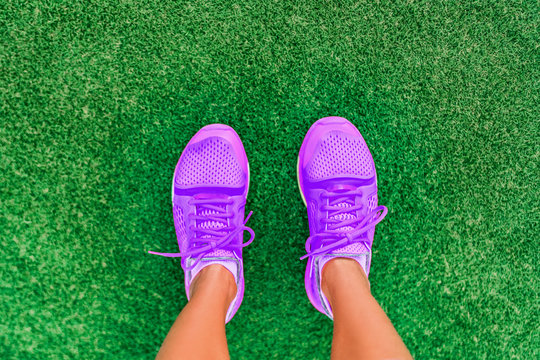 Fitness lifestyle active girl top view of running shoes woman standing on grass. pov selfie of feet during exercise run workout outdoors. Sport footwear.