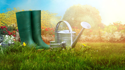 Spring garden. Boots and gardening tools in green grass.