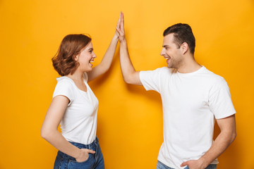 Excited beautiful couple wearing white t-shirts standing Wall mural