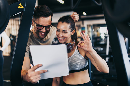 Male fitness gym instructor resting and smiling with young attractive woman while making workout plan.