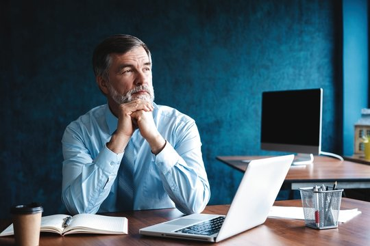 Focused mature businessman deep in thought while sitting at a table in modern office.