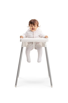 Baby girl sitting in a baby chair and crying