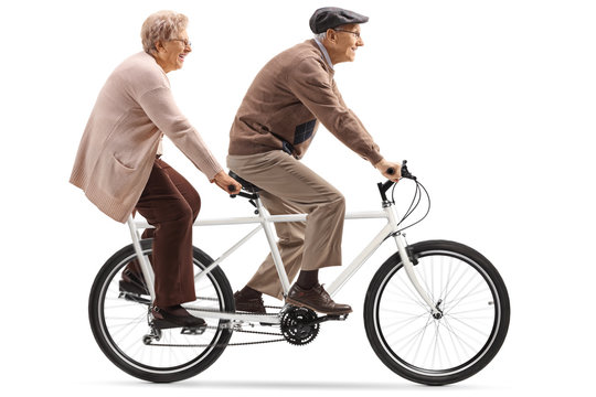 Senior man and woman riding a tandem bicycle