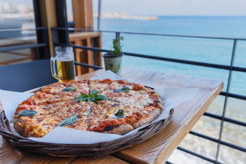 delicious pizza with salami on a wooden table in the seaside cafe of the Greek town of Hersonissos