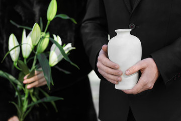 Couple with mortuary urn and flowers at funeral