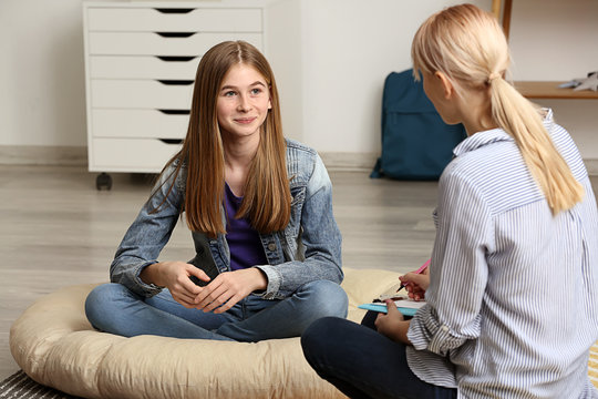 Female psychologist working with teenage girl in office