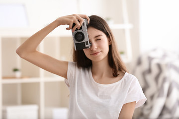 Young girl with photo camera at home
