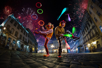 Night street circus performance whit clown, juggler. Festival city background. fireworks and Celebration atmosphere. Fotomurales