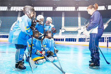 Hockey players listening to coach during training