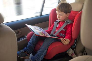 Toddler boy reading book in child car seat