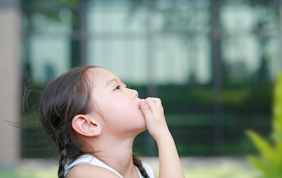 Child girl intend sucking her fingers.