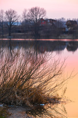 Landscape with the image of spring lake at sunset