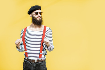 Portrait of a stylish bearded man dressed in striped shirt, suspenders and hat on the yellow background outdoors Wall mural