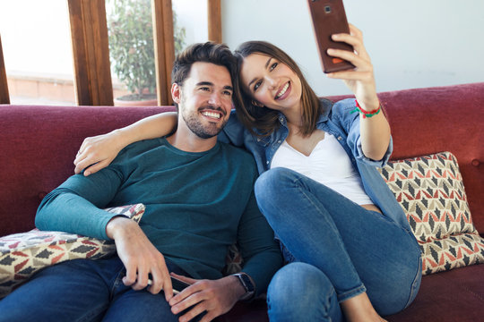 Happy young couple taking a selfie with smart phone while sitting on sofa at home.