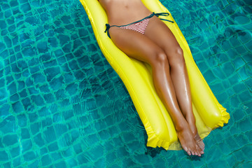 Stylish fashionable tanned lady in a striped bikini lying on a yellow inflatable mattress in a pool in a luxury hotel, concept of relaxation, travel, enjoyment