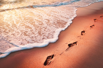 Foot print on sand beach with smooth wave abstract texture background.