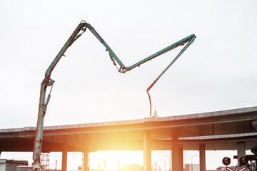 Pouring concrete with a concrete pump at a construction site. The concept of construction work, design, architecture.