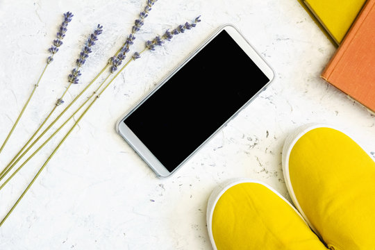 Smart phone template, yellow shoes, dry flowers and books on gray stone background. Top view. Active lifestyle concept.