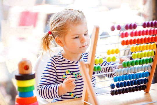 Adorable cute beautiful little toddler girl playing with educational wooden rainbow toy pyramid and counter abacus. Healthy happy baby learning to count and colors, indoors on sunny day.